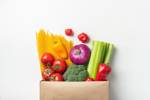Bolsa de papel de diferentes alimentos saludables en una mesa.