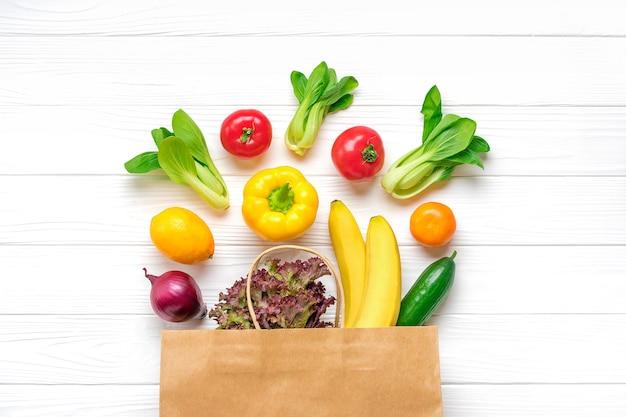Bolsa de papel ecológica completa de diferentes alimentos saludables: pimiento amarillo, tomates, plátanos, lechuga, verde, pepino, cebolla vista superior endecha plana compras