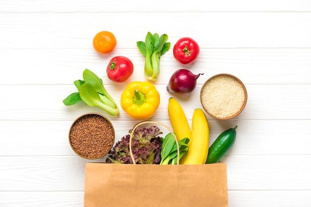 Bolsa de papel ecológica completa de diferentes alimentos saludables: trigo sarraceno, arroz, pimiento amarillo, tomates, plátanos, lechuga, verde, pepino, cebolla vista superior endecha plana compras