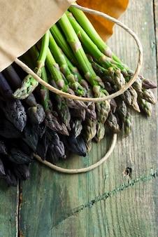 Bolsa de papel ecológico con espárragos de espárragos morados y verdes naturales orgánicos caseros frescos sobre un fondo de madera.