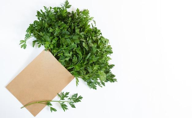 Bolsa de papel ecológico con perejil fresco aislado sobre fondo blanco, vista aérea