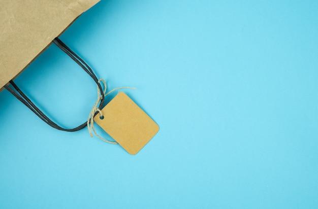 Bolsa de papel con etiqueta sobre fondo azul. etiqueta sin texto. concepto de compras. copia espacio