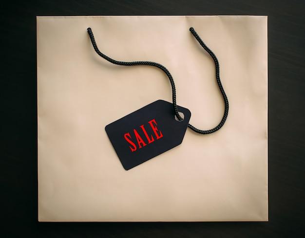 Bolsa de papel con etiqueta viernes negro aislado sobre fondo negro, de cerca.