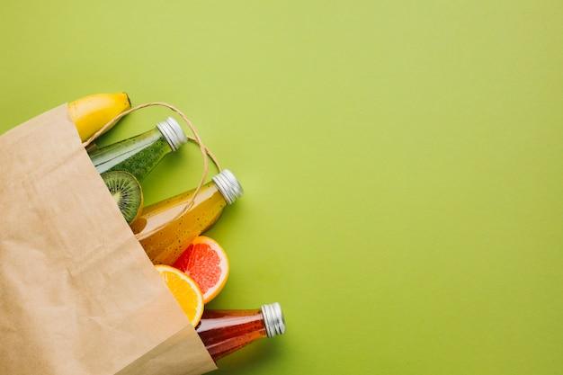 Bolsa de papel flatlay con frutas y jugos.