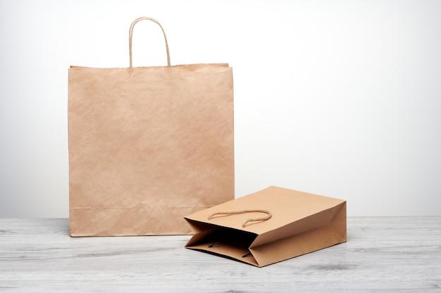 Bolsa de papel grande y pequeña con asas aisladas. bolsa de papel kraft sobre mesa de madera.