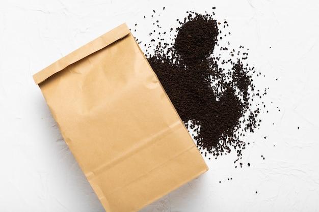 Bolsa de papel con granos de café en polvo.