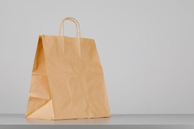 Bolsa de papel marrón con asas, bolsa de compras vacía con área para su logotipo o diseño, concepto de entrega de alimentos.