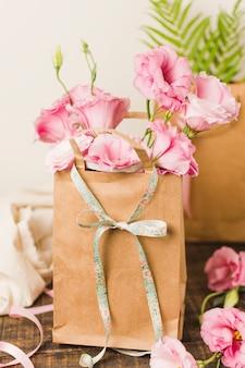 Bolsa de papel marrón con flor de eustoma rosa fresca en mesa de madera