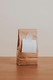 Bolsa de papel marrón con un papel de carta blanco en blanco