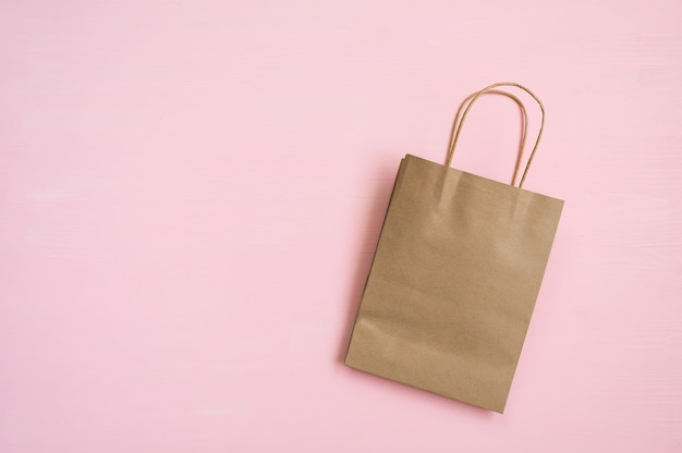 Bolsa de papel marrón vacía con asas para ir de compras sobre un fondo rosa