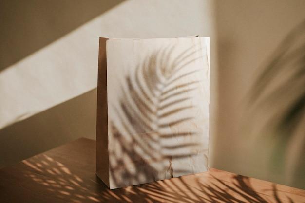 Bolsa de papel natural con sombra de hojas de palmera