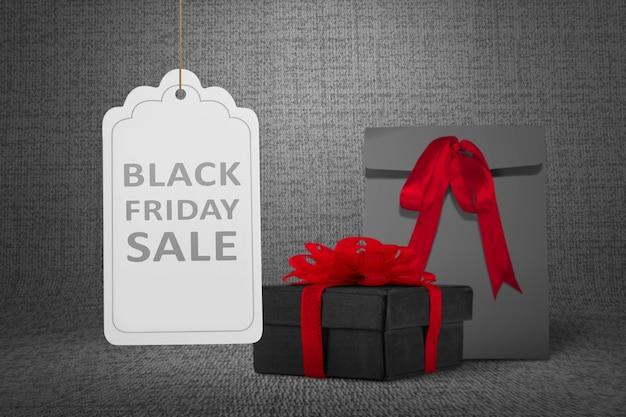 Bolsa de papel negra y caja de regalo con cinta roja.