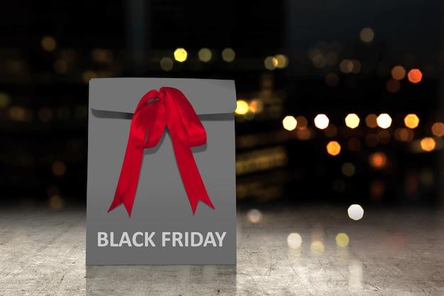 Bolsa de papel negra con una cinta roja con texto black friday