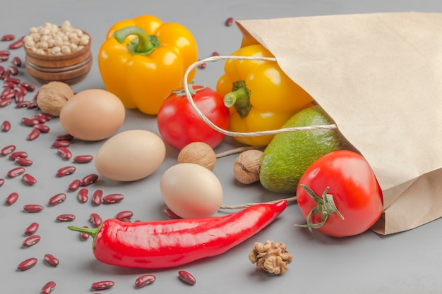 Bolsa de papel con nueces, garbanzos, frijoles, lentejas, pimientos, tomates, aguacate sobre un fondo gris