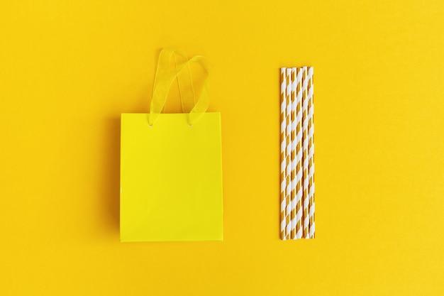Bolsa de papel de regalo y pajitas con rayas doradas sobre fondo amarillo. concepto de fiesta, fiesta, cumpleaños. imagen sin sombra con espacio de copia para su texto. vista superior y endecha plana.