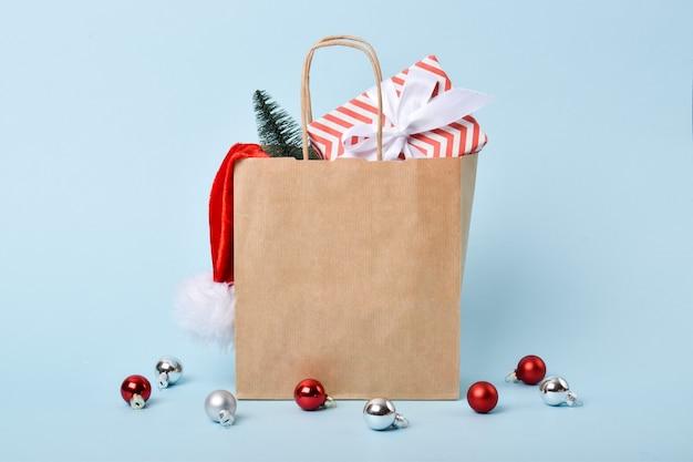 Una bolsa de papel con regalos y adornos navideños. preparación para el año nuevo y navidad. entrega.