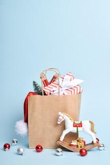 Una bolsa de papel con regalos, un gorro de navidad y un árbol de navidad. feliz año nuevo 2022 y navidad.