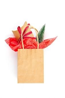 Bolsa de papel con regalos de navidad, árbol de navidad y decoración.