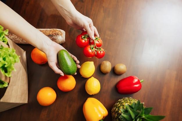 Bolsa de papel de supermercado y mesa llena de frutas y verduras después de comprar