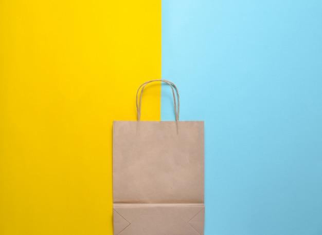 Bolsa de papel vacía sobre un fondo pastel azul amarillo. tendencia de minimalismo. vista superior.