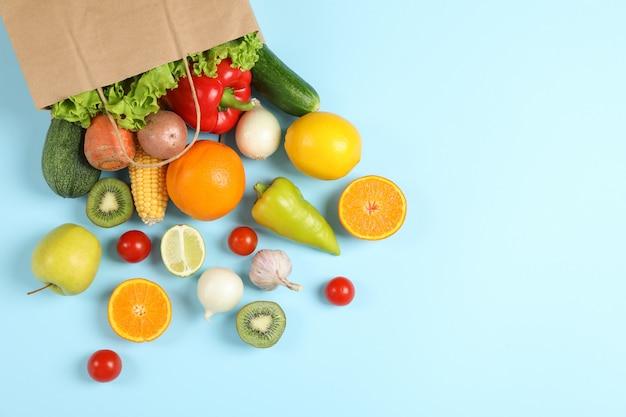 Bolsa de papel, verduras y frutas en el espacio azul para texto