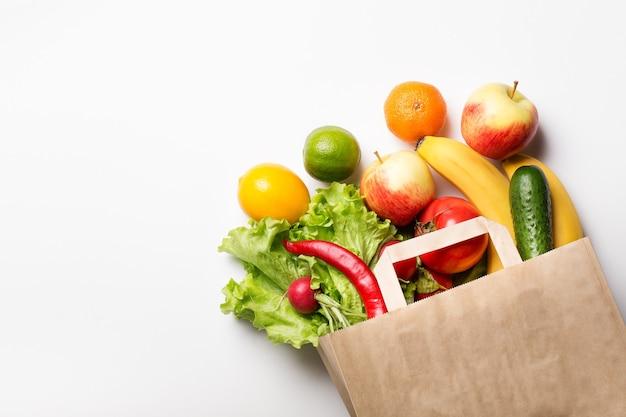 Bolsa de papel con verduras y frutas sobre un fondo blanco. pedidos en línea en una tienda de comestibles. el concepto de nutrición adecuada. entrega de comida.