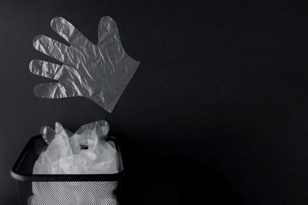 Bolsa de plástico con asas, guantes en el contenedor sobre un fondo negro.