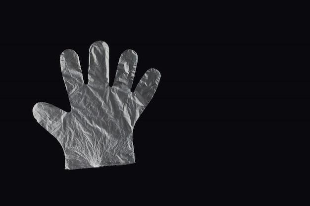 Bolsa de plástico con asas, guantes, sobre fondo negro