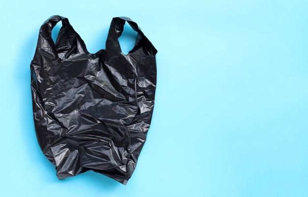 Bolsa de plástico negra sobre fondo azul.