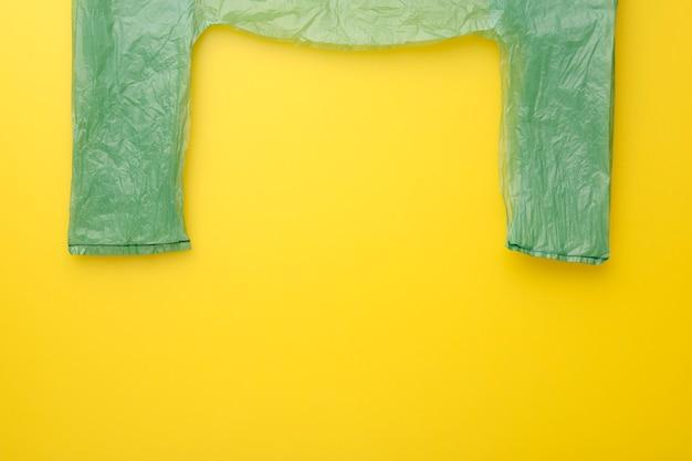 La bolsa de plástico verde en el fondo amarillo, recicla concepto. vista superior.