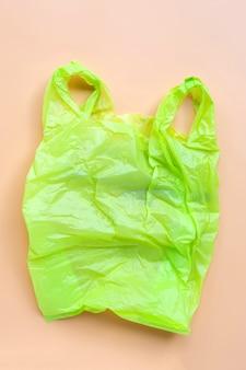 Bolsa de plástico verde sobre fondo amarillo. concepto de contaminación ambiental.
