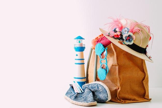 Bolsa de playa hipster con artículos para un día en la playa sobre fondo blanco