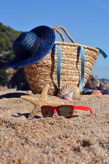 Bolsa de playa con un libro y un teléfono y gafas de sol acompañados de una estrella de mar.