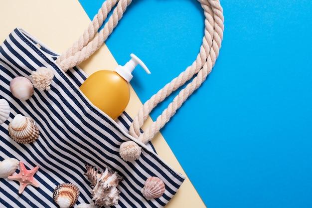 Bolsa de playa pelada con crema solar y concha.