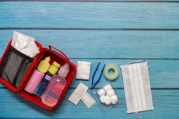 Bolsa de primeros auxilios para niños en vista superior con suministros médicos en madera.