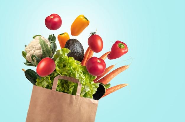 Bolsa reciclable de verduras frescas sobre fondo azul cielo de verano