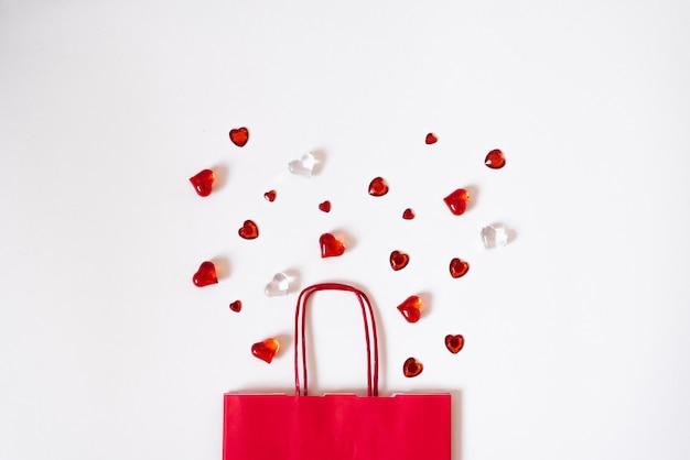 Bolsa de regalo con corazones dispersos sobre un fondo blanco. el día de san valentín es un concepto real