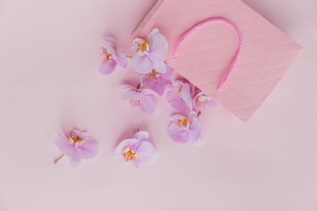 Bolsa de regalo rosa y flores de orquídeas voladoras sobre una superficie de color rosa claro. tarjeta de felicitación de vista superior con delicadas flores. vacaciones, día de la mujer, concepto de saludo del día de la madre.