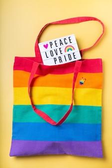 Bolsa reutilizable de arco iris de texto de orgullo de amor de paz sobre fondo amarillo