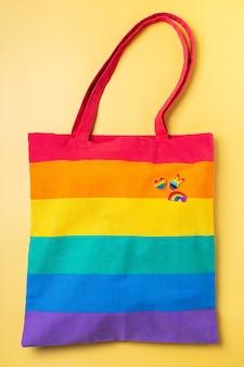 Bolsa reutilizable arcoíris con insignias lgbtq sobre fondo amarillo