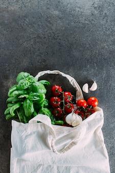 Bolsa reutilizable con comestibles. bolso tote, mínimo desperdicio. albahaca fresca, tomates cherry, ajo en bolsa de tela.