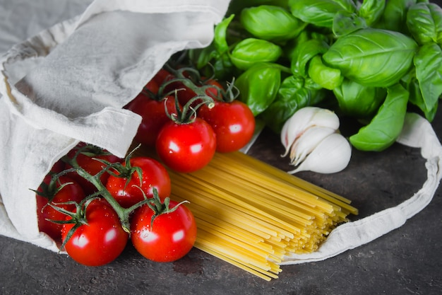 Bolsa reutilizable con comestibles. bolso tote, mínimo desperdicio. albahaca, tomates cherry, ajo en bolsa de tela.