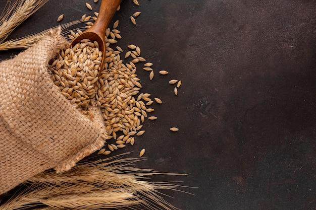 Bolsa de semillas de trigo y cuchara de madera.