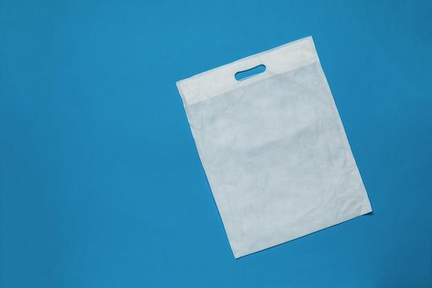 Bolsa de supermercado blanca sobre un fondo azul.