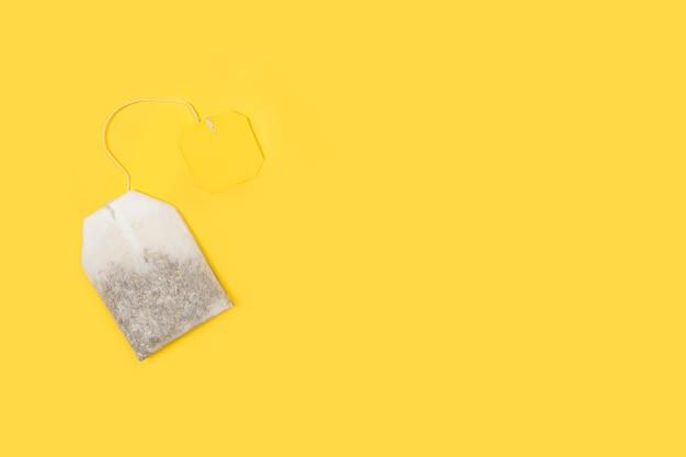Una bolsa de té con una etiqueta amarilla sobre un fondo amarillo en una vista superior con espacio de copia