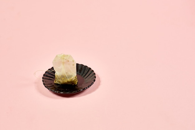 Bolsa de té usada sobre un platillo negro sobre un rosa.