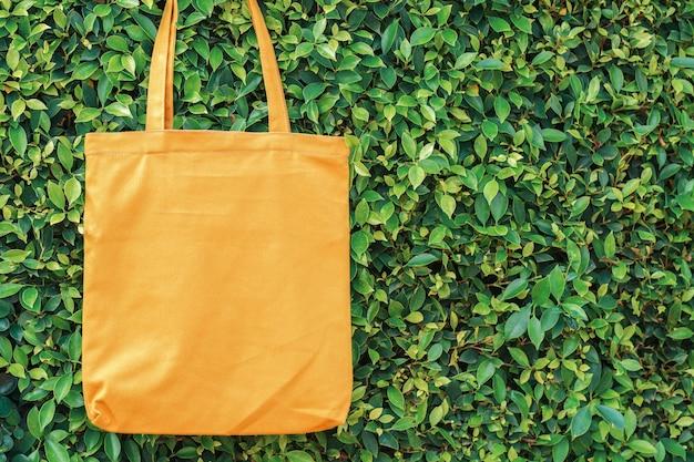 Bolsa de tela amarilla colgando sobre fondo de hoja verde