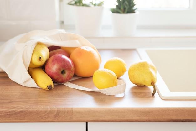 Bolsa de tela llena de frutas frescas en la encimera de la cocina