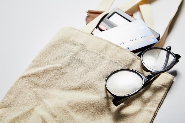 Bolsa de tela con tarjeta de crédito y cartera en blanco.