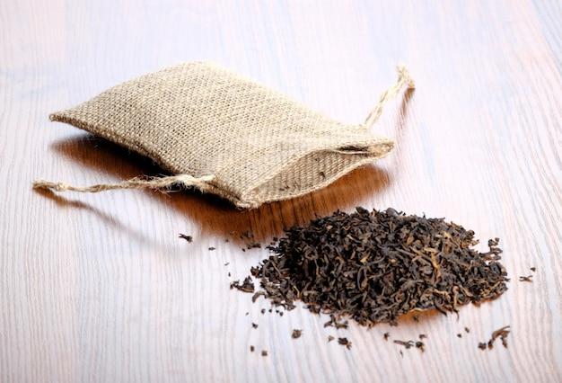 Bolsa de tela y té seco sobre suelo de madera.